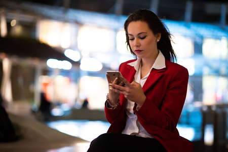 Woman using her smatphone outdoor in the evening in a modern city setting 免版税图像 - 154905997