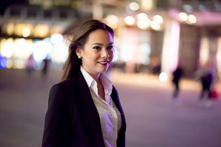 Businesswoman walking in a city at night time