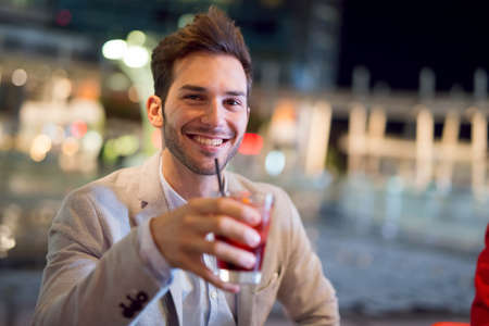 Smiling man drinking a cocktail 免版税图像 - 154906058