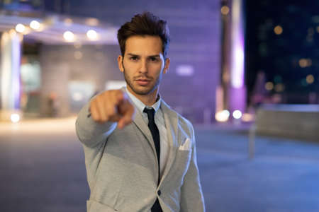 Man pointing his finger at you in a nocturnal city setting