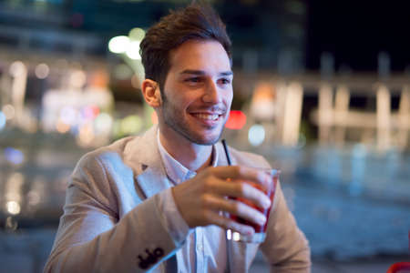 Smiling business man drinking a cocktail after work