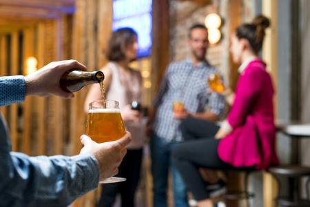 Ein Bier servieren, während Freunde trinken und lächeln