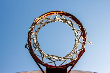 Vintage basketball ring in a street courts with a blue sky background. Down view. Selective Focus. Фото со стока