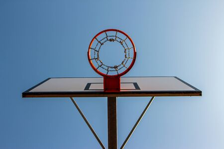 Basketball ring with a blue sky background in a street basketball court. Down view.