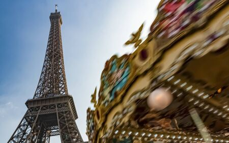 Eiffel tower, blue sky background, moving carousel in the foreground