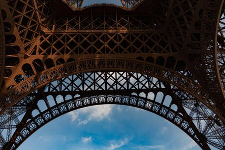 View from beneath Eiffel Tower with beautiful patterns and blue sky background