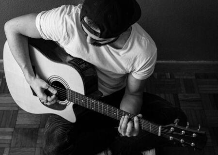 Junger Mann mit Mütze und weißem T-Shirt, der sich darauf konzentriert, eine Akustikgitarre zu spielen, sitzt auf dem Boden. Selektiver Fokus. Getreide. s&w. Standard-Bild