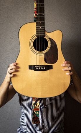 Young man with a colorful shirt and vintage rings covers his face with a guitar. Grey background. Grain. Selective focus. Фото со стока