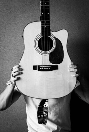 Young man with a white t-shirt and vintage rings covers his face with a guitar. B&W. Grain. Selective focus. Фото со стока
