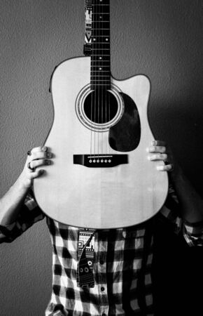 Young man with a checkered shirt and vintage rings covers his face with a guitar. B&W. Grain. Selective focus. Фото со стока