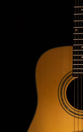 Acoustic guitar close-up view with a black background. Selective focus. Copy Space.