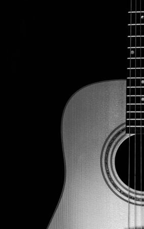 Acoustic guitar close-up view with a black background. Selective focus. B&W. Copy Space.
