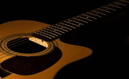 Acoustic guitar close-up view with a black background. Selective focus.