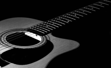 Acoustic guitar close-up view with a black background. Selective focus. B&W. Stock Photo
