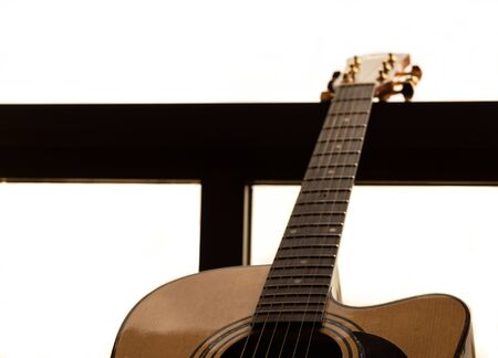 Guitar in a window, Overexposed background. Selective focus. Copy space. Stock Photo
