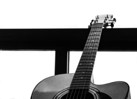 Guitar in a window, Overexposed white background. Selective focus. B&W. Copy Space.