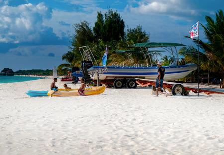 Zanzibar, Tanzania. July 21, 2018: Three dark-skinned boys play on the beach in a boat on a sunny day. Coast of the Indian Ocean