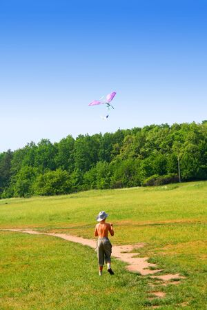 Childhood. Road to the sky. Kid with the flying kite.