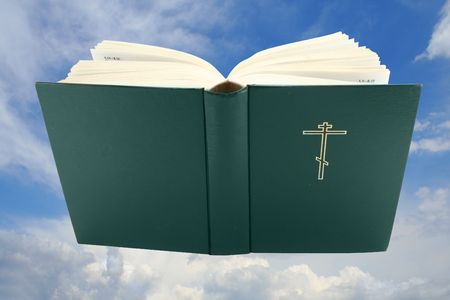 Opened holy bible over sky Stock Photo