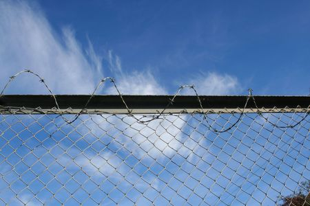 Fence - barbed wire over the blue sky Stock Photo