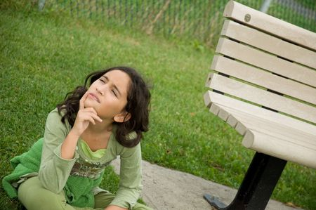 sitting on the ground: A girl sitting on the ground next to a bench. Stock Photo