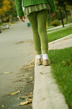 A girl balancing her self on the sidewalk. photo