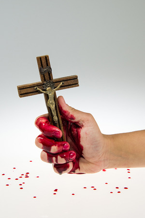 Hand covered with blood is holding a cross on white and gray gradient background. 版權商用圖片