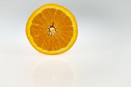 golden dusk: Half of an orange on white and grey gradient background. Stock Photo