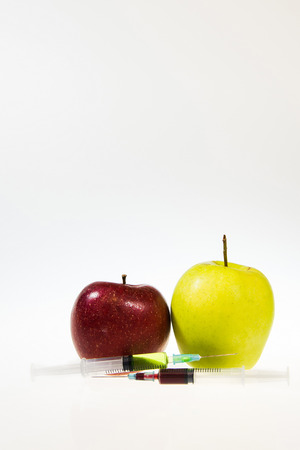 apple gmo: Two syringes with chemicals next to the two apples. White and grey gradient background. High res photo taken with a full frame Nikon D610.