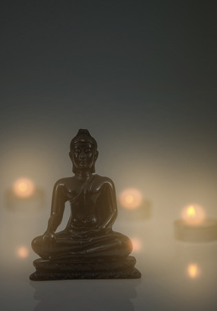statuary garden: Little Buddha figure with candle lights behind and white and grey gradient background. High res photo taken with a full frame dslr. Stock Photo