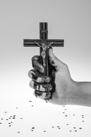 Hand covered with blood is holding a cross on white and gray gradient background. photo