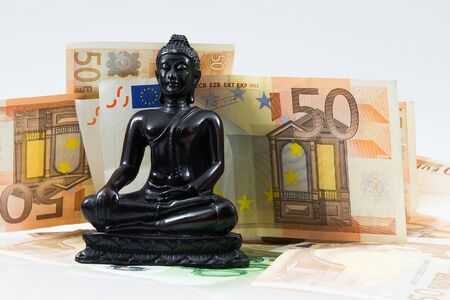 res: Little Buddha figure sorrounded by euro currency notes with white background. High res photo taken with a full frame camera.