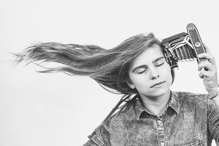 moskva: Teenager girl shooting at herself with an old folding camera. Stock Photo