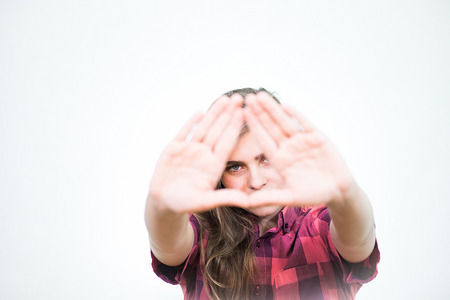 illuminati: Young teenage girl is showing the Illuminati triangle symbol. White background behind her.