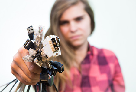 entangled: Young and angry girl is holding bunch of entangled cables in her hands. Stock Photo