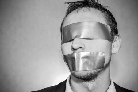 guardar silencio: Foto de un hombre joven con cinta adhesiva cubriendo su boca Foto de archivo