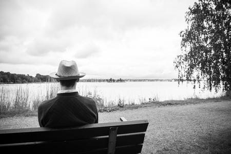 hombre solo: Hombre joven en el banco que mira al horizonte hermoso