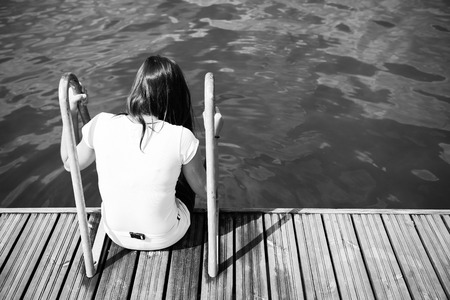 Girl sitting on the pier. Muddy water is visible. Whole scene is somewhat sad and provokes reflection.