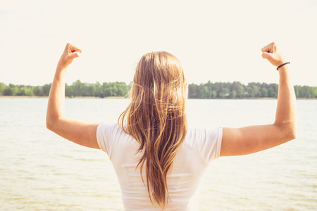 Girl is pointing her hands towards the sky in the manner of success, she's standing in the water. Archivio Fotografico