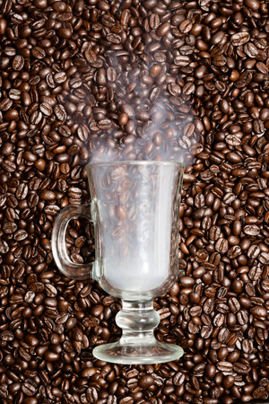 coffee beans: Irish coffee glass stuck in fresh coffee beans. Smoke is coming out of the glass.