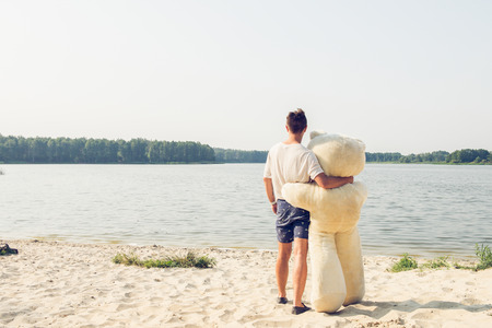 speed dating: Handsome young man is fooling around with his massive teddy bear.