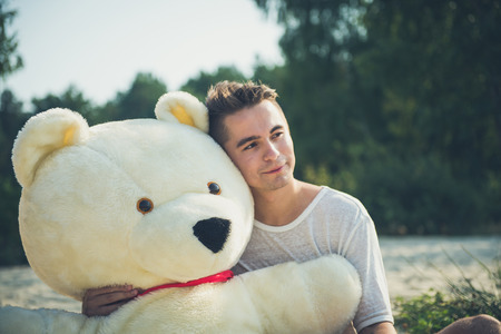 Handsome young man is fooling around with his massive teddy bear.