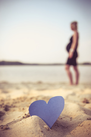 parentage: Photo of a heart stuck in the sand and a pregnant lady in the background. Stock Photo