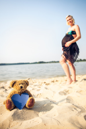 parentage: Photo of a teddy bear in the foreground and beautiful pregnant woman in the background.