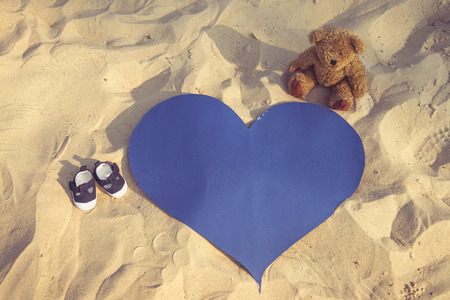 parentage: Photo of the tiny shoes, teddy bear and a big blue heart on a beach.