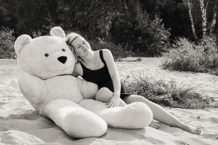 speed dating: Portrait of a young and beautiful pregnant woman with a big teddy bear.