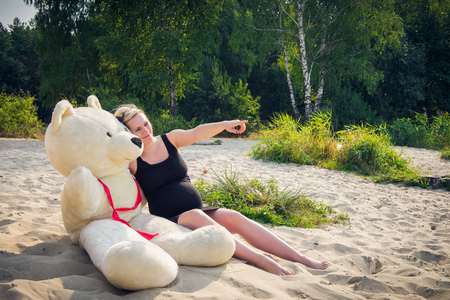 parentage: Portrait of a young and beautiful pregnant woman with a big teddy bear.