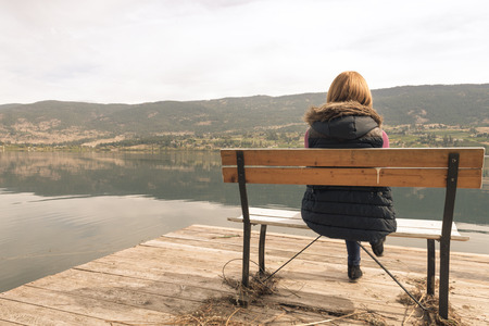 Beautiful girl on a bench looking at the lake Stock Photo
