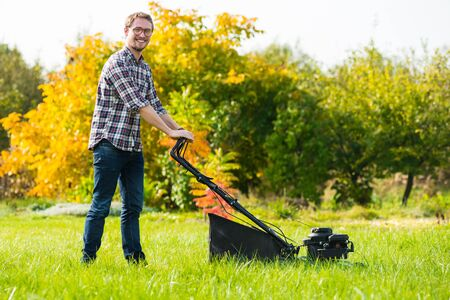 Photo of a young man mowing the grass during a sunny day.