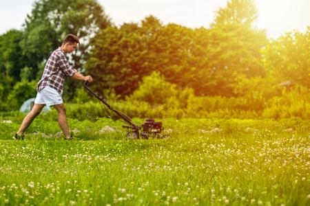 Handsone 젊은 남자가 잔디를 깎고있다 스톡 콘텐츠